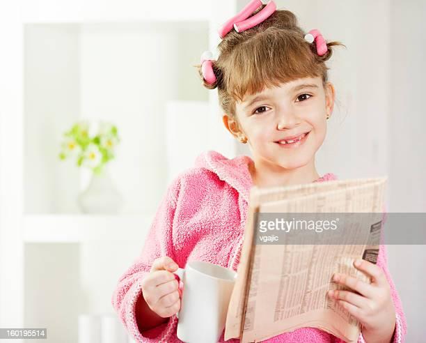 child reading newspapers and drink tea - krulspelden stockfoto's en -beelden