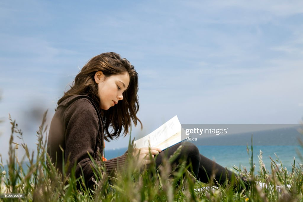 Child reading poetry by the sea : Stock Photo