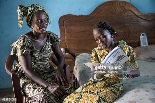 A child reading to her mother in their local Wolof language The children's books in the local language was developed and printed by TOSTAN to help...