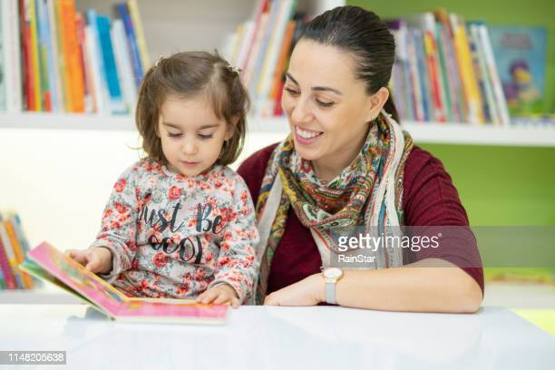 child reading with a preschool teacher - preschool building stock pictures, royalty-free photos & images