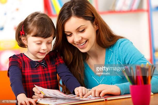 Child reading with a preschool teacher
