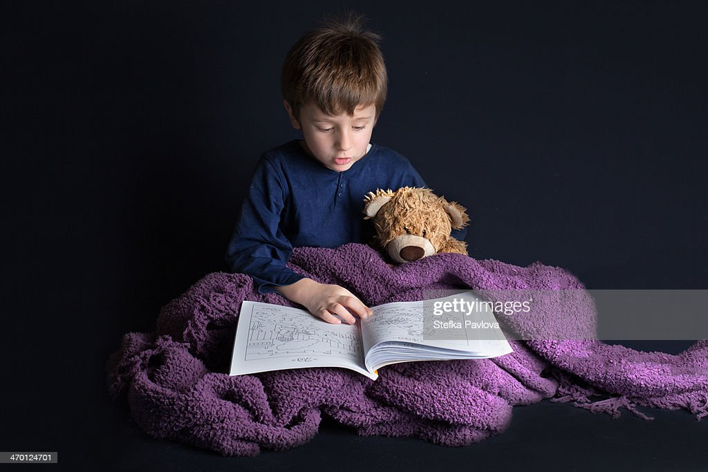 child reads a bedtime story to his teddy bear : Stock Photo