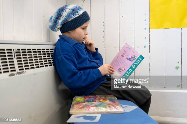 Child reads a Roald Dahl book at Roath Park Primary School on February 23, 2021 in Cardiff, Wales. Children aged three to seven began a phased return...