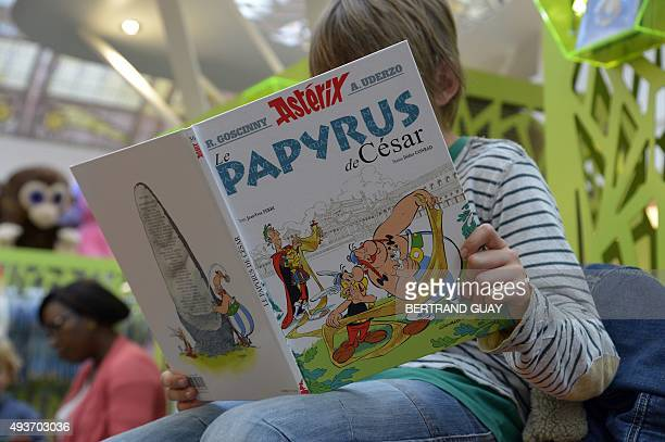 A child reads the new Asterix album 'Asterix and the missing scroll' on October 22 2015 in Paris on the day of its release The 36th edition in the...
