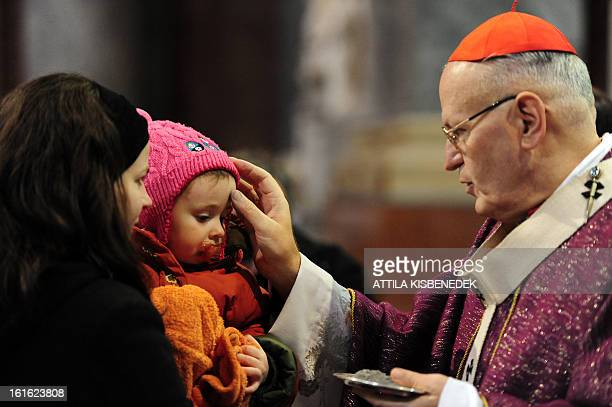 Child receives ash by Archbishop of Esztergom-Budapest, Hungarian Peter Erdo in the major Hungarian church, the Esztergom Basilica at the beginning...