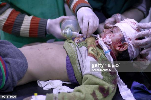 A child receives medical treatment as he lies unconscious at a field hospital as Assad Regime forces carried out airstrikes over Arbin town of the...