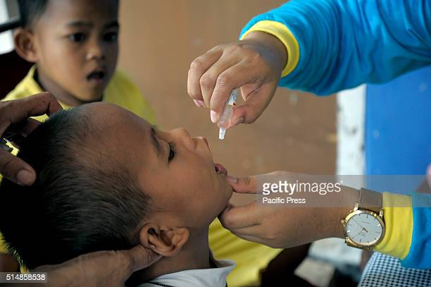 Child receiving oral polio drops. After being declared polio-free by World Health Organization officials in 2014, Indonesia is observing National...