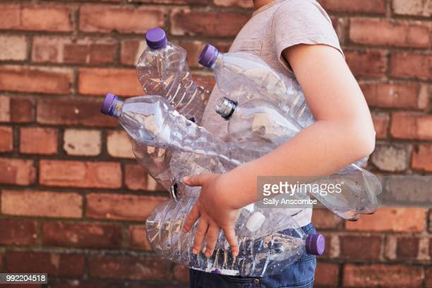 child recycling plastic bottles - sustainability stock photos and pictures