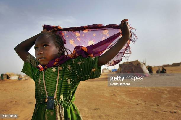 A child refugee from the Darfur region of Sudan wears a protective Islamic amulet called a 'hijab' as she walks near her family's tent home on August...