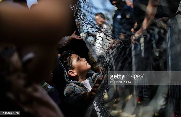 A child refugee looks at a police barricade as people push to open the GreekMacedonian border at their makeshift camp in the northern border village...