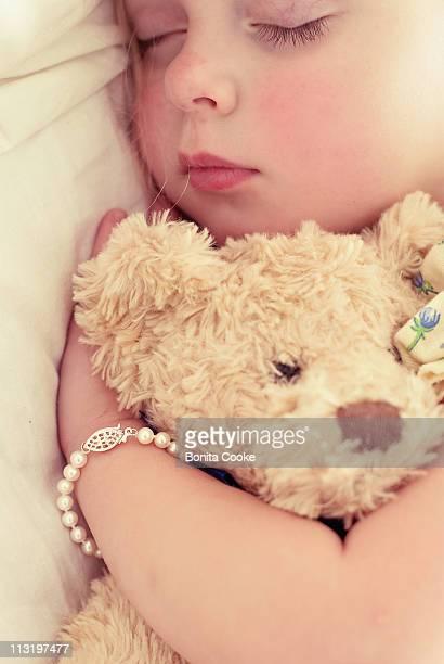 Child resting holding her teddy bear