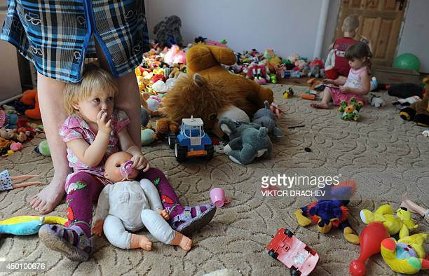A child rests against her mother's legs as they reside in a hostel and temporary shelter organized for people displaced by ongoing violence in the...