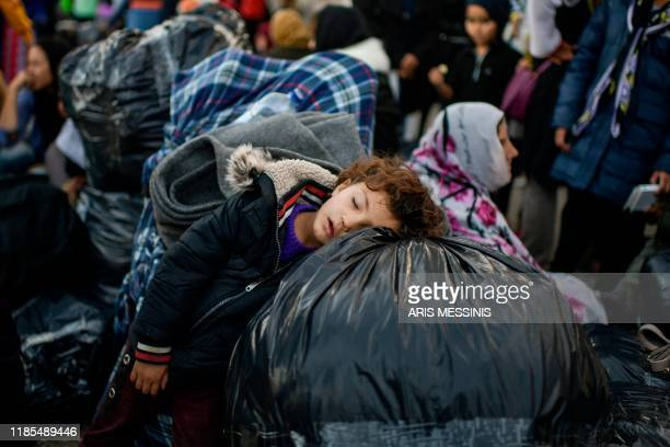 Child rests on bags as migrants and refugees wait to depart from the Greek island camp of Moria on Lesbos to Athens on November 29, 2019. -...