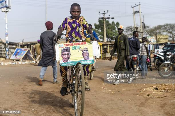 TOPSHOT A child rides a bicycle bearing a campaign poster of candidate of the ruling All Progressives Congress party President Mohammadu Buhari in...