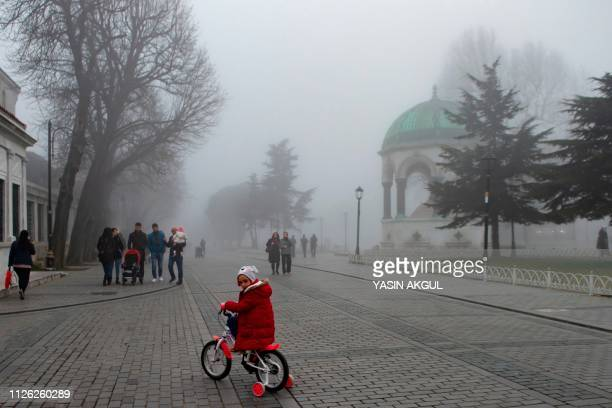 A child rides a bicycle on Sultanahmet Square near the Blue mosque on a foggy day in Istanbul on February 20 2019