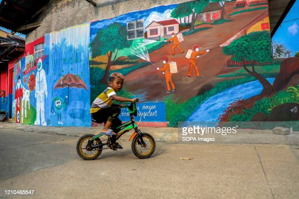 Child rides a bicycle past a coronavirus awareness graffiti during a lockdown. Indonesian local artists drew murals on the walls of the houses for...
