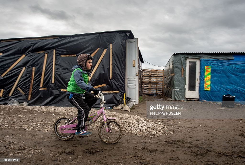A child rides a bike in front of a shelter used as a school in the so-called 'Jungle' migrant camp in Calais, northern France, on February 6, 2016. HUGUEN