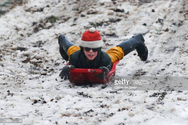 Child rides a sledge down a snowy hill at Swan Pool Park, on December 28, 2020 in Stourbridge, England. Heavy snow fall has covered the West Midlands...