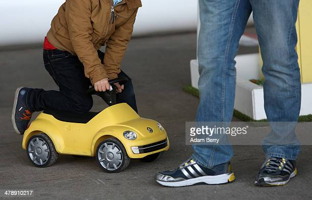 Child rides a toy Volkswagen Beetle at the Electric Mobility Week , a public Volkswagen event at the former Tempelhof airport, on March 15, 2014 in...