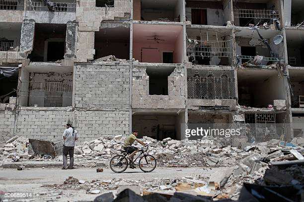 A child rides by a bombdamaged building in the Hanano neighbourhood of Aleppo on June 3 2014 Hanano has been one of the districts worst affected by...