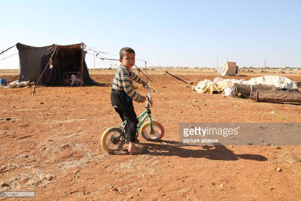 A child rides his bicycle on the grounds of a camp built by displaced people near a Turkish observation point after they were forced to leave the...