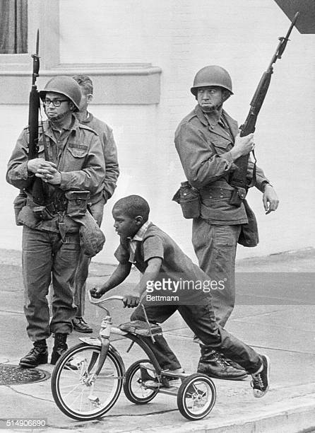 A child rides his tricycle past soldiers called in to keep the peace after three days of violence in the wake of the assassination of Dr Martin...