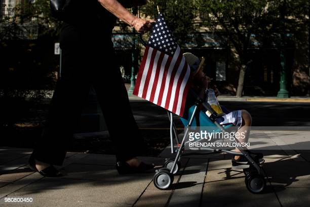 A child rides in a stroller with a US flag during a rally to protest the process of separating children from adults during detention when they cross...