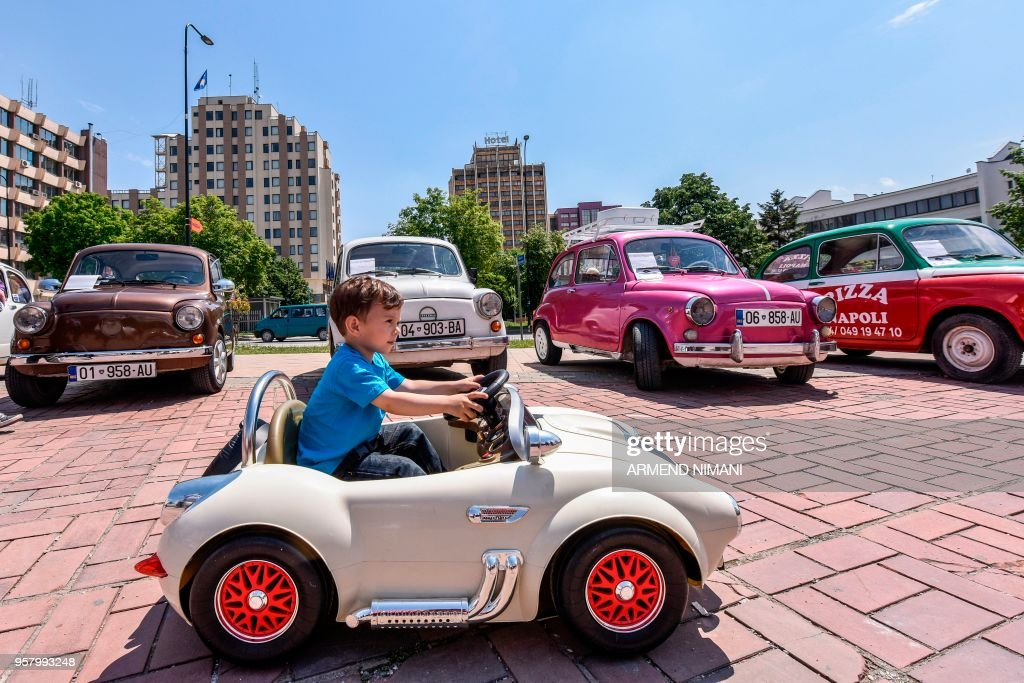 A child rides in his toy car past old timer Zastava cars, a version ...