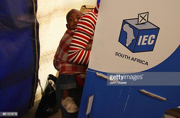 A child rides on his mother's back as she votes in national elections on April 22 2009 in the Sweetla Squatter Camp near Alexandra Township South...