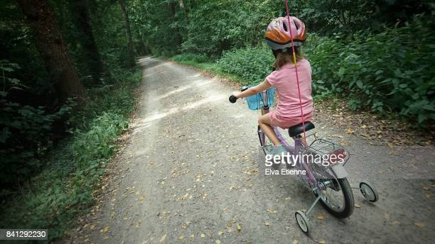 Child riding a bicycle with stabilisers, along a forest path in Germany