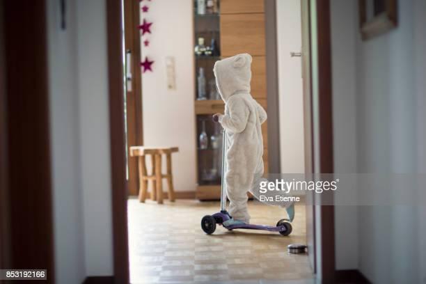 child (4-5) riding a push scooter in a house - travessura imagens e fotografias de stock