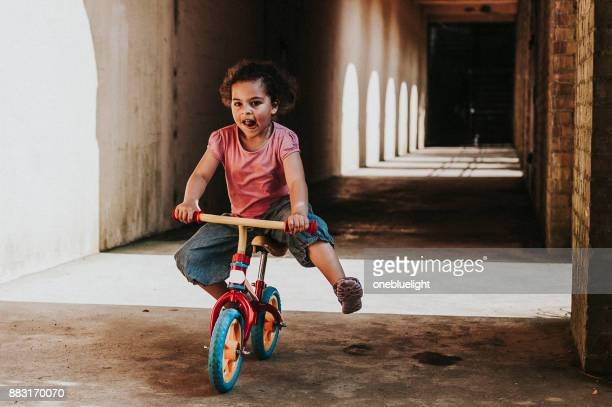 child (4-5) riding balance bike. - onebluelight stock pictures, royalty-free photos & images