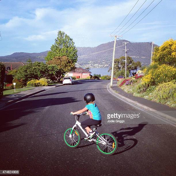 Child riding bicycle along suburban street