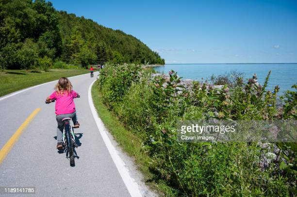 child riding bicycle on lake shore road on mackinac island - mackinac island stock pictures, royalty-free photos & images