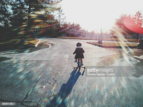 Child Riding Bicycle On Road Against Clear Sky