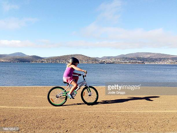 Child riding bike along dirt track near river