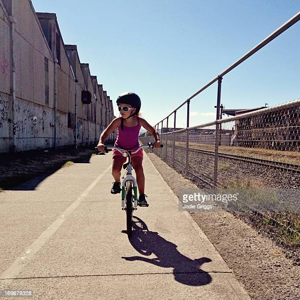 Child riding bike along path in industrial area