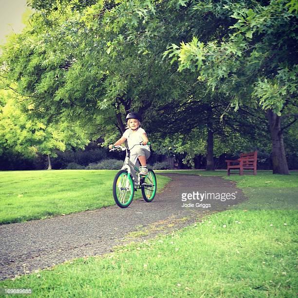 Child riding bike along path through trees