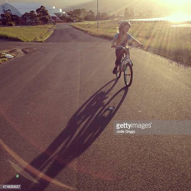 Child riding bike along road in late afternoon sun