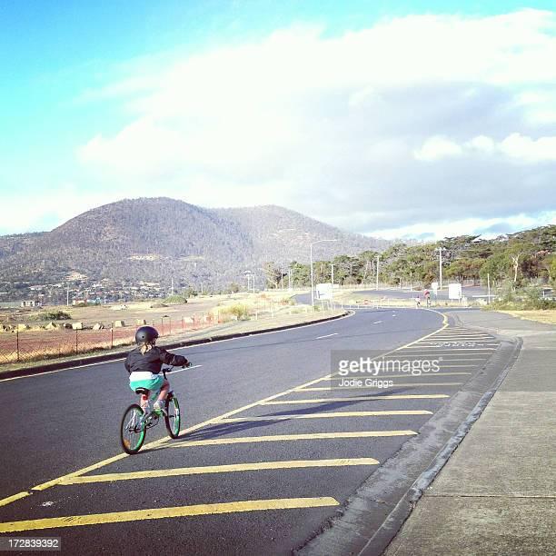 Child riding bike beside road