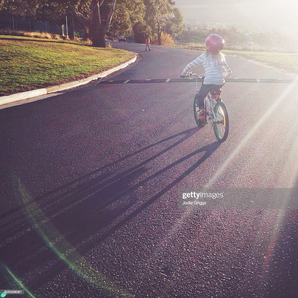 Child riding bike outside in late afternoon sun : Stock Photo