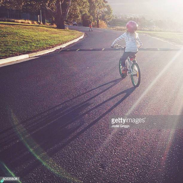 Child riding bike outside in late afternoon sun