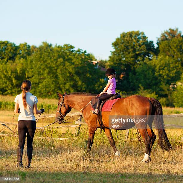 Child Riding Horse Outdoors.