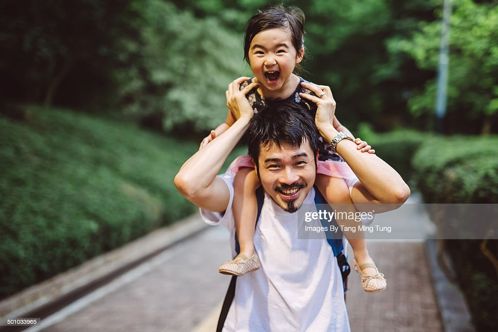 Child riding on dad's shoulders joyfully in park : Stock Photo