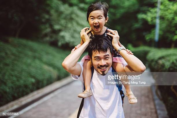 Child riding on dad's shoulders joyfully in park
