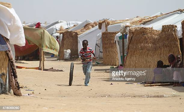 N'DJAMENA CHAD JUNE 21 A child rolls a tyre among the tents in a refugee camp near the capital N'Djamena Chad on June 21 2015