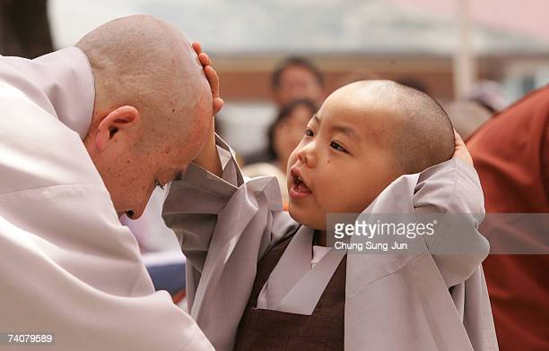 A child rubs his and a monk's head during the 'Children Becoming Buddhist Monks' ceremony at a Chogye temple on May 5 2007 in Seoul South Korea The...