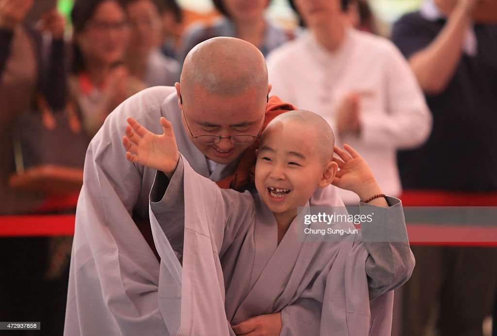 A child rubs his head after a Buddhist monk shaved his hair off during the 'Children Becoming Buddhist Monks' ceremony forthcoming buddha's birthday at a Chogye temple on May 11, 2015 in Seoul, South Korea. Children have their hair shaved off during the 'Children Becoming Buddhist Monks' ceremony ahead of buddha's birthday at a Chogye temple. The children will stay at the temple to learn about Buddhism for 14 days. Buddha was born approximately 2,559 years ago, and although the exact date is unknown, Buddha's official birthday is celebrated on the full moon in May in South Korea, which is on May 25 this year.