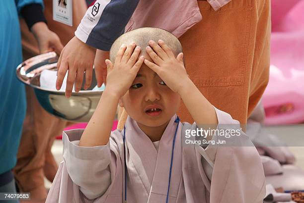 A child rubs his head after a Buddhist monk shaved his hair off during the 'Children Becoming Buddhist Monks' ceremony at a Chogye temple on May 5...