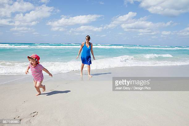 Child running and crying on the beach with her mother